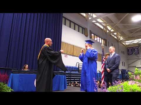 A student at Carmel High School receives his diploma with help from his fellow classmates.