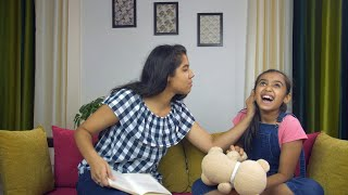 Young female kid teasing her elder sister while sitting in a living room