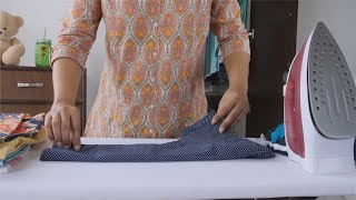 Shot of an Indian woman folding pressed shirt of her child