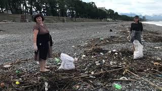 После шторма на пляже Кобулети люди собирают грецкие орехи