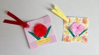 画用紙にマスキングテープを貼って作ったカードに、折り紙のカーネーシ...