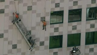 Workmen Rescued After Dangling Off Side of High-Rise