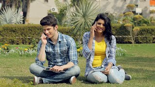 A girl and a boy sitting together outside in a park and talking on their cellphones