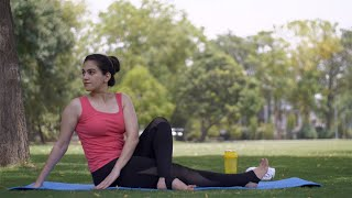 Healthy beautiful lady practicing Matsyendrasan Asana (half twist pose) on a yoga mat - sportswear