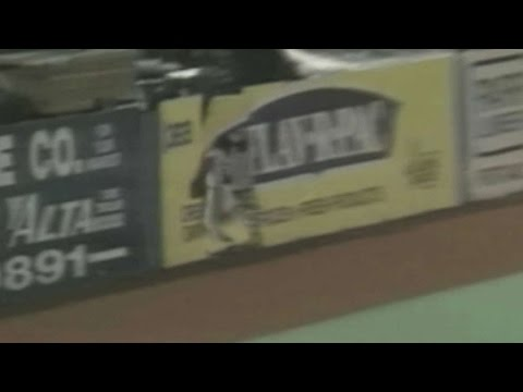 Rodney McCray crashes through the outfield fence