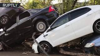 Dozens of cars were swept away and piled up after massive mudflows ...