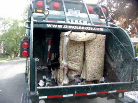 What Does A Trash Compactor Do crushing a huge 4 seat sofa to fit into a garbage can using a