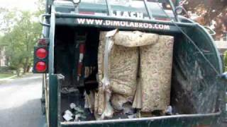 Crushing a huge 4 seat sofa to fit into a garbage can using a compacting garbage truck