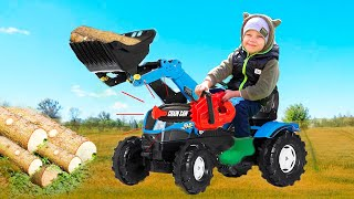 Малыш ездит на синем тракторе с ковшом и наехал колесом на бревно