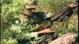 Gambar cover Soldiers apply dye and mud on uniform and weapons for camouflage in the United St...HD Stock Footage