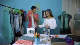 Indian male designer showing his new collection of dresses to his customers - fashion studio