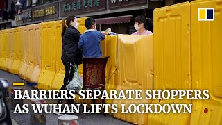 Wuhan residents shop across tall barriers as the city lifts restrictions
