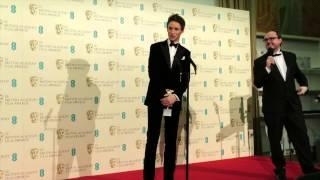 Eddie Redmayne talks backstage at the 2015 BAFTA Awards. The Theory of Everything