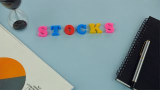 "Closeup shot of the word ""Stocks"" on a blue platform - business and finance concept"