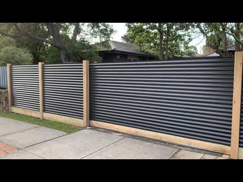 Corrugated steel exposed post fence with sleeper. Automatic sliding gate.