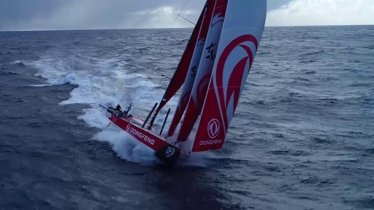 Drone shots of Dongfeng surfing fast, triple-heading, with dark clouds behind them. Stern cam as a big waves washes the helmsman off the whee. Can't see who it was; Daryl helps them back onto the wheel. Crew in the cockpit; washing machine. Night vision stern cam shot with snow/hail falling. Snow collected in the foot of the reefed main.