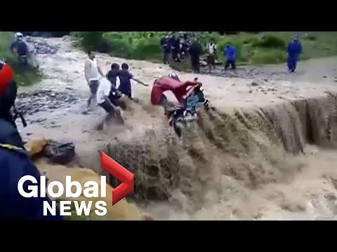 Floodwaters push motorcyclist