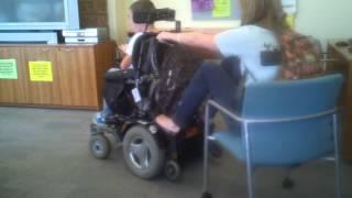 Shane pulling Sarah in his wheelchair.