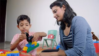 Shot of an Indian mother playing colorful blocks with her son - Summer holiday homework