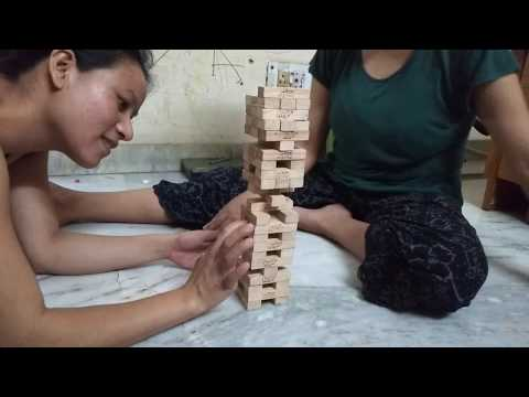 Cute two girls playing Jenga game at home
