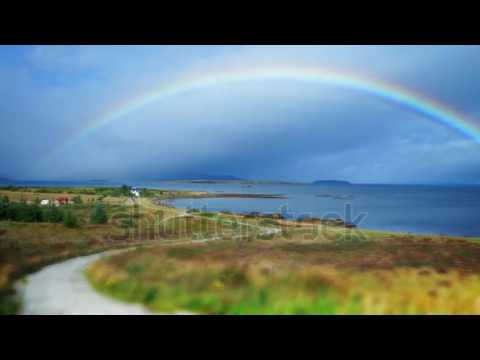 Rainbow over village in Scotland time lapse