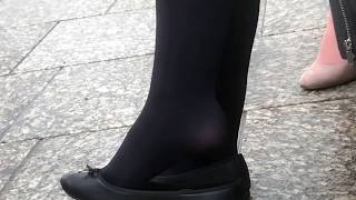 Young woman dangling flats in tights