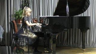 София играет на рояле в музыкальной школе. Ребенок играет на пианино. Фортепиано для начинающих