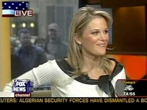 Newswoman bending over in a black leather skirt