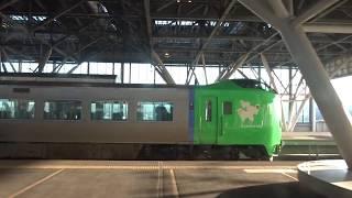 旭川駅を出発する特急ライラック789系の車窓から見た停車中の特急ライラックと真っ白な大雪山系の山々
