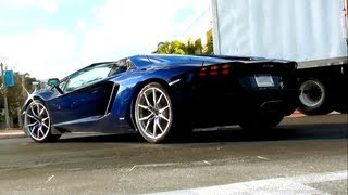 Two Dark Blue Lamborghini Aventador LP700-4 Roadsters driving in Miami Beach Florida