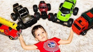 Artem plays at home hide-and-seek with small toy cars