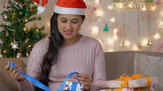 Beautiful Indian women in Santa hat opening Christmas gift