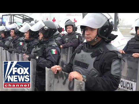 Mexican police in riot gear line up at US border