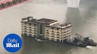 Bizarre moment a building FLOATS downstream in China