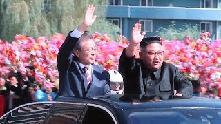 Kim and Moon wave from their car as crowds line the roads of Pyongyang