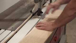 Ripping A Straight Edge On White Oak With Sliding Table Saw With Safety Hold Down Clamp.