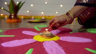 Diwali festival - Hands of a traditional female with bangles decorating rangoli with a Diya