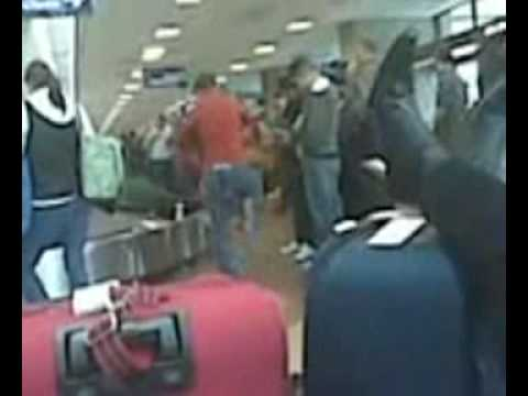woman kicks baby to swing him over her shoulder at salt lake city airport.