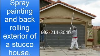 Spray painting and back rolling exterior of a stucco house.