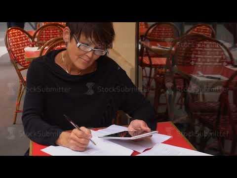 Slow motion Aged business woman use tablet for writing finance declaration