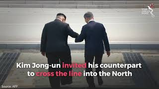 Moon and Kim shake hands over the border between North and South