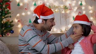 Indian man / father putting a red Christmas cap on her daughter