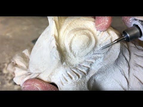 Crafting an owl sculpture out of birch wood