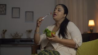 Overweight Indian woman eating a healthy organic green salad at home - Health concept