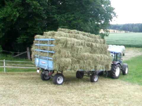 new holland traktor zieht heuwagen youtube. Black Bedroom Furniture Sets. Home Design Ideas