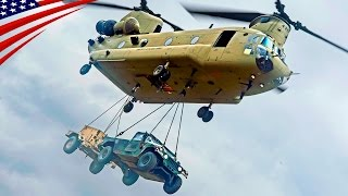 A CH-47 Chinook heavy-lift helicopter transports a military weapons...