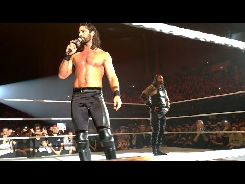 Seth Rollins stands with Roman Reigns in Lille, France