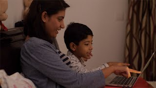 Side shot of an Indian mother and son watching cartoon story movie on the laptop - Technology in your bedroom