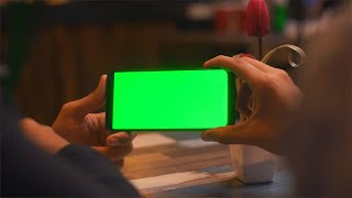 Closeup shot of Indian couple's hands holding a blank green screen mobile phone