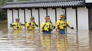 Typhoon Hagibis: Japanese rescue workers wade through muddy waters searching for survivors